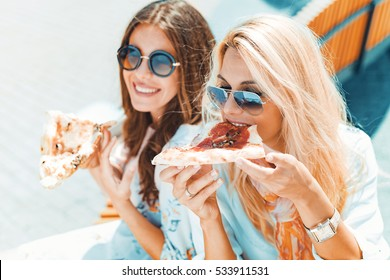 Portrait of two young women eating pizza outdoors,having fun together.