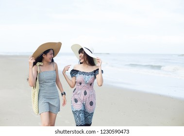 portrait of two young women friends laughing and walking on the beach