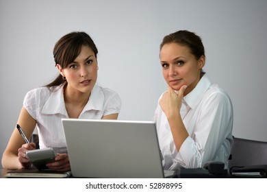 Portrait of two young women in front of a laptop computer