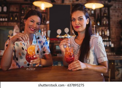 Portrait of two young women having cocktail drinks in pub