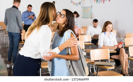 Portrait of two young women meeting in lecture hall, kissing each other on cheek