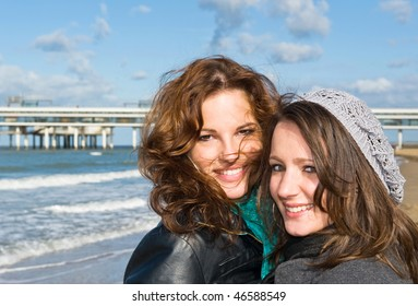 Portrait of two young women on the beach on a beautiful autumn afternoon