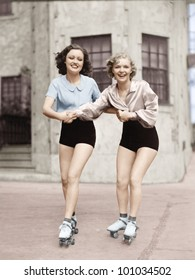 Portrait of two young women with roller blades skating on the road and smiling