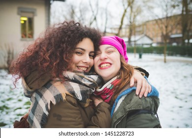 portrait of two young women standing in park and hugging – vacation, togetherness, winter