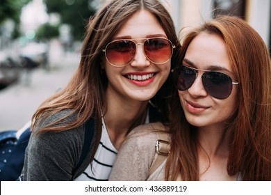 Portrait of two young women wearing sunglasses in the city. Close up