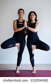 Portrait of two young yogi women practising yoga, wearing black sportswear, white studio background, tree pose (selective focus)
