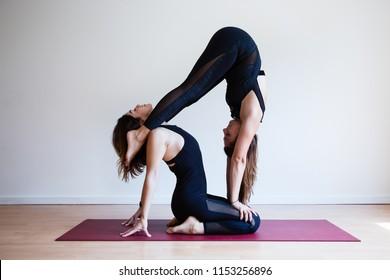 Portrait of two young yogi women practising acro yoga, wearing black sportswear, white studio background (selective focus)
