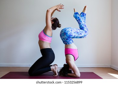 Portrait of two young yogi women practising yoga, wearing colorful sportswear, white studio background, headstand pose (selective focus)
