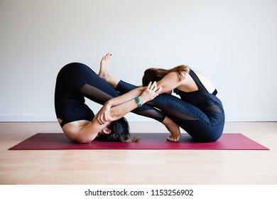 Portrait of two young yogi women practising yoga, wearing black sportswear, white studio background, eternity pose (selective focus)