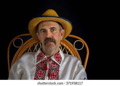 Portrait of Ukrainian country-man sitting in a wicker chair, wearing straw and traditional clothes (Vyshyvanka)