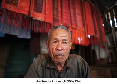 Portrait of an Ulos cloth craftsman. Ulos is a typical cloth of the Batak tribe, Samosir, Indonesia, circa September 2018