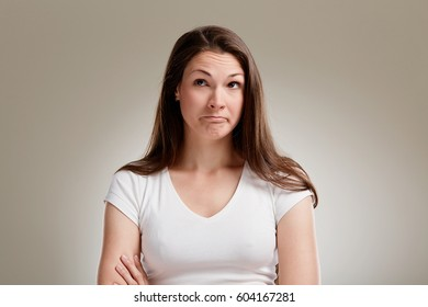 Portrait of uncertain woman with long brunette hair on neutral background
