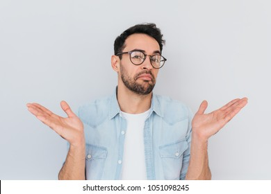 Portrait of uncertain young stylish stubble man with trendy round glasses wears demin blue shirt, shrugs shoulders being puzzled or confused. Caucasian unsure male make gestures doubtfully with hands.