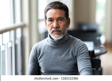 Portrait of unhappy angry mature asian man with stylish short beard looking at cemera with negative suspicious. Casual retired hispanic people feeling worry or unpleasant at outside cafe concept.