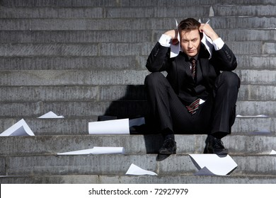 Portrait of unhappy businessman under depression touching his head in grief