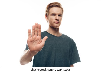 Portrait of Unhappy Casual Man Showing Stop Sign. Attractive Young Guy Do No Gesture with Dismiss Denial Expression Isolated on White Background. Concept of Human Emotions