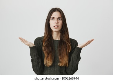 Portrait of unhappy confused and questioned attractive young girl holding her palms up, isolated over white background. Woman has no clue why her boyfriend is angry at her.