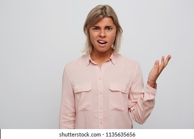 Portrait of unhappy confused young woman with blond hair and braces on teeth wears pink shirt feels embarrased and holding copyspace on palm isolated over white background