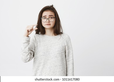 Portrait of unhappy cute girl with messy hair and glasses showing something tiny or small, looking bothered because of it, isolated over white background. Student shows amount of work she finished