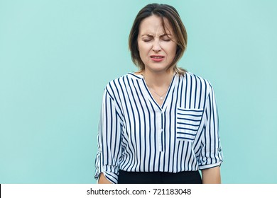 Portrait of unhappy and depressed woman with blonde hair feeling ashamed or sick, keeping eyes closed. Human face expressions and emotions concept. Isolated studio shot on light blue background.