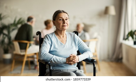 Portrait of unhappy disabled senior woman in wheelchair looking at camera with sadness in nursing home, other aged patients in background