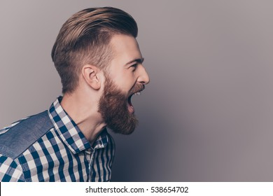portrait unhappy furious businessman open mouth and shouting, isolated gray wall