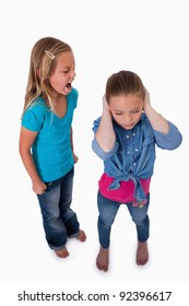Portrait of an unhappy girl screaming at her friend against a white background