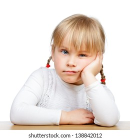 Portrait of unhappy little girl sitting at desk with hand on chin