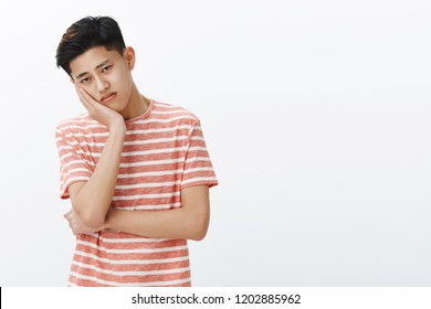 Portrait of unhappy lonely and sad young bored asian guy leaning head on palm looking with upset indifferent gaze at camera feeling uneasy, feeling tired of boring lecture posing over white background