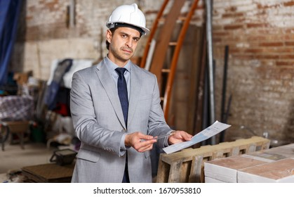 Portrait of unhappy man in suit and helmet holding paper at construction site