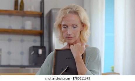 Portrait of unhappy mature lady holding wooden frame with photo of deceased friend of family and hugging in feeling lonely and depressed standing at home