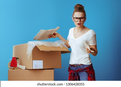 Portrait of unhappy modern woman in white t-shirt near cardboard box with a broken dish on blue background
