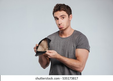 Portrait of an unhappy sad man showing empty wallet over white background