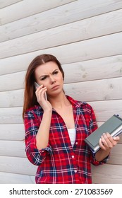 Portrait of unhappy student girl with books, talking on the phone