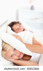 Portrait of an unhappy woman awaken by her fiance's snoring in their bedroom