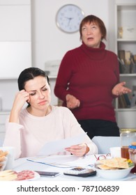 Portrait of unhappy woman with documents at table, family quarrel