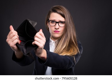 Portrait of unhappy young woman holding empty wallet as spent too much or not enough cash concept