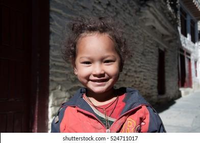 Portrait of unidentified happy smiley little Nepalese girl in Marpha Village, Dhawalagiri Zone of northern Nepal, 28 September, 2012