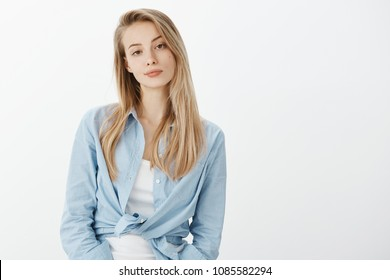 Portrait of unimpressed attractive stylish woman with blond hair, smirking and looking indifferent at camera, being careless and uninterested in topic of conversation over white wall