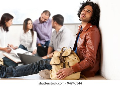 portrait of a university student with his friends in the background, group of multiethnic students, left out student