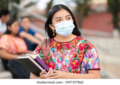 Portrait of a university student wearing a medical mask to protect himself from the flu virus, pandemic COVID-19 in the university building. Back to school.