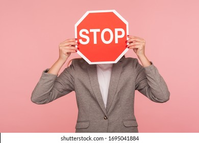 Portrait of unknown business person in suit jacket covering face with Stop symbol, anonymous woman holding red traffic sign stop, warning of danger, restriction and limits. indoor studio shot isolated