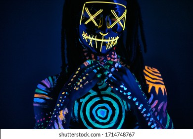 portrait of unrecognizable incognito male in UV mask, fluorescent paint on shirtless skin glows in dark space