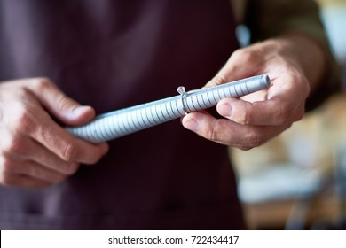 Portrait of unrecognizable jeweler checking ring size with special tool in workshop