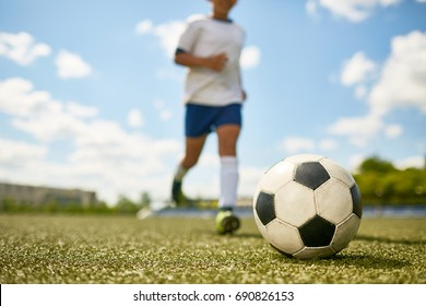 Portrait of unrecognizable teenage boy running in field to kick the ball during football practice, focus on football  ball
