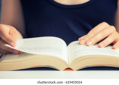 Portrait of unrecognizable woman reading a book at home