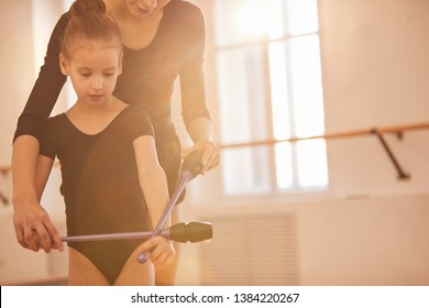 Portrait of unrecognizable woman teaching little girl doing gymnastics moves with clubs in studio lit by warm sunlight, copy space