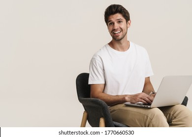 Portrait of unshaven excited man working with laptop while sitting on armchair isolated over white background