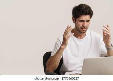 Portrait of unshaven irritated man working with laptop while sitting on armchair isolated over white background