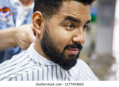 Portrait of unshaven young African man sitting in chair covered with blanket at barbershop salon while barber prepares his hair for cutting.Male beauty treatment process.Cut new haircut & trim beard